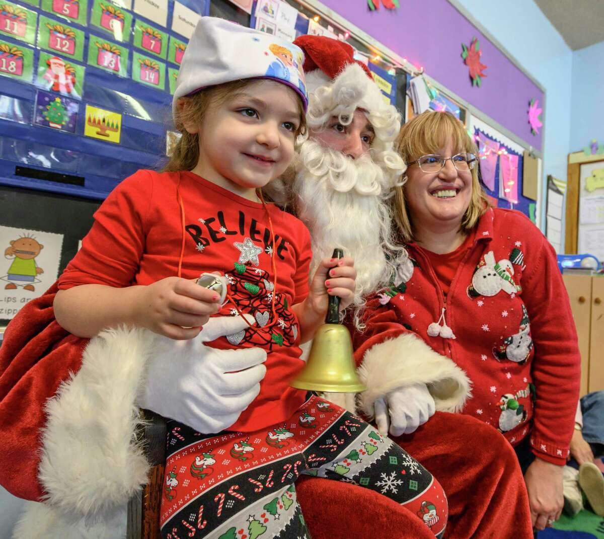 Santa a.k.a Rafael Levy-Lesko has a photo op with student Zoe Nash, left and her mom Sue Hash, right, as he makes a visit to teacher Jami Sousis' Pre School Class at A Child's Place, Unity House Wednesday Dec. 18, 2018 in Troyi, N.Y. (Skip Dickstein/Times Union)