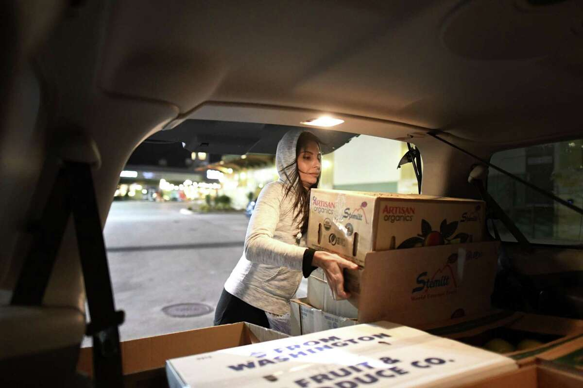 Leslie Murphy, one of the founders of the nonprofit Champions Domain, loads donated fruit from Trader Joe's into her vehicle for distribution to people in need.