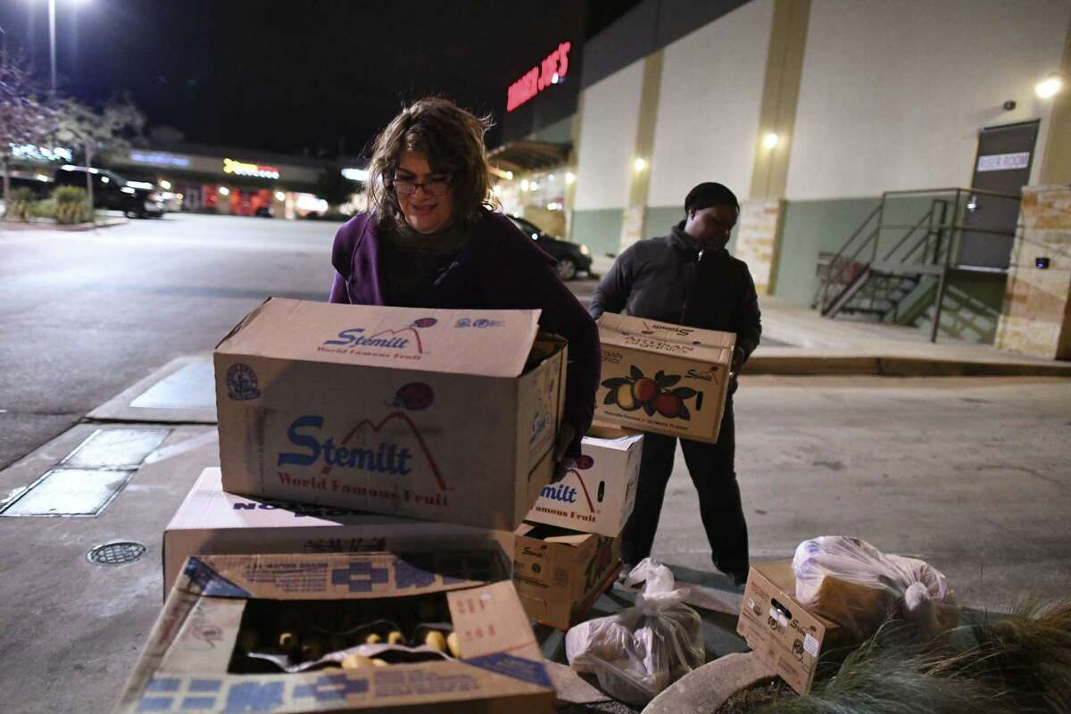 Pam Allen, founder of Eagles Flight Advocacy & Outreach, picks up a load of donated fruit at Trader Joe's on Thursday. The food will be donated to families in need.