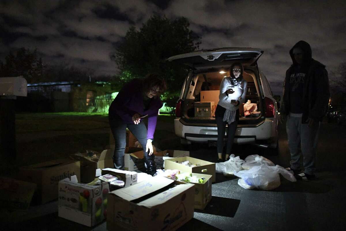 Pam Allen, left, and Leslie and Mike Murphy sort food for distribution on a West Side street on Thursday.
