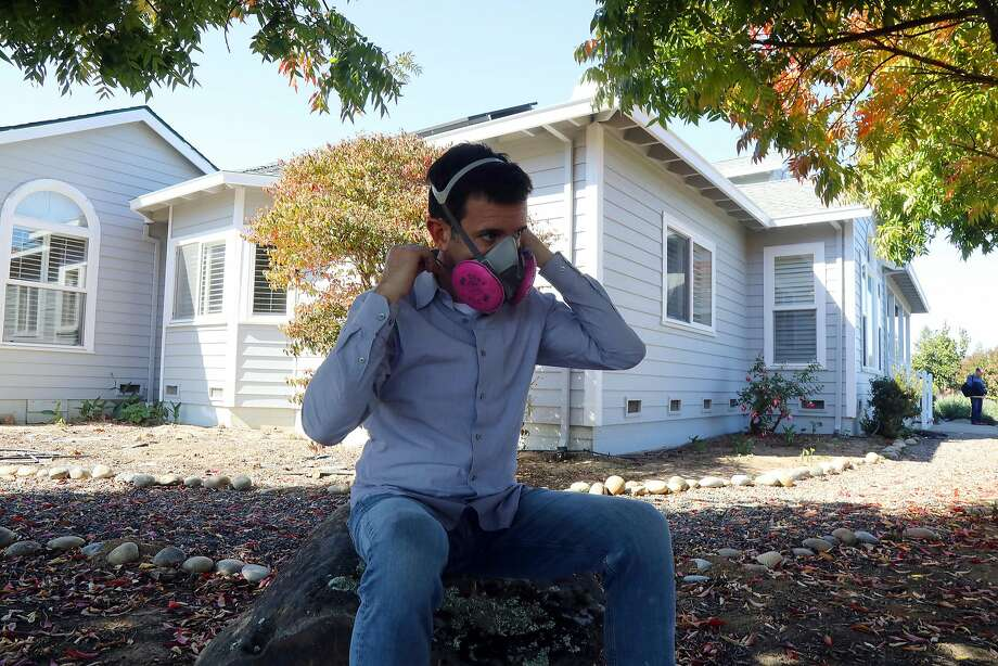"Robert Guthrie wears a respirator outside his home in Sebastopol. His neighbors are commercial growers. The smell is ""beyond anything you would imagine,"" his wife Grace says. Photo: Jim Wilson / New York Times"