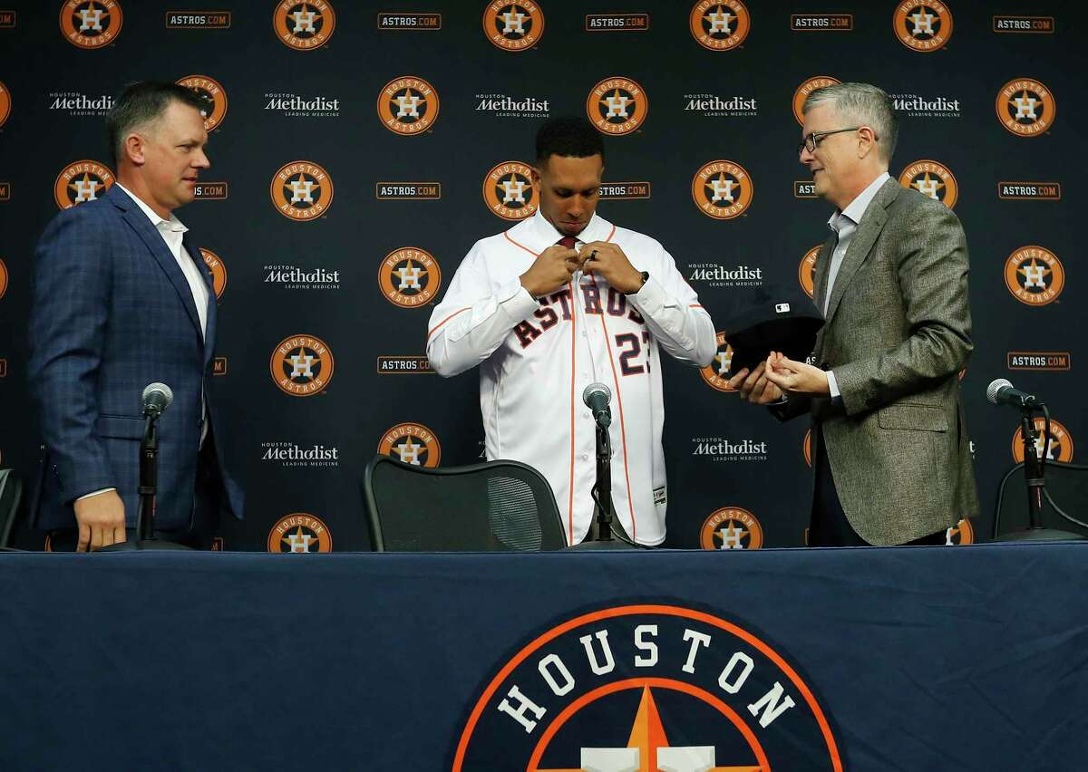 Michael Brantley puts on his Astros jersey as manager A.J. Hinch and Astros President of Baseball Operations and General Manager Jeff Luhnow look on as they announced the signing of Brantley at Minute Maid Park, Wednesday, Dec. 19, 2018, in Houston. Brantley signed a two-year contract with the outfielder.