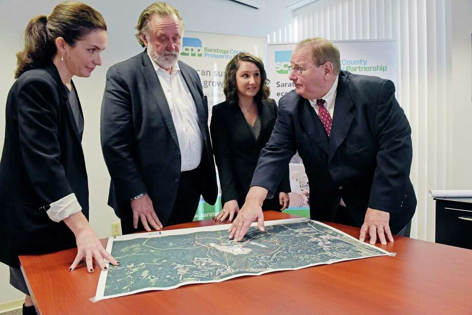 Shelby Schneider, left, VP of Saratoga County Prosperity Partnership, Marty Vanags, second from left, president of Prosperity Partnership and Jennifer Kelley, third from left, an economic development assistant with Prosperity Partnership, look over a map of Luther Forest with Kelley's father,  Jack Kelley, director of economic development at Prime Companies, on Wednesday, Dec. 19, 2018, in Malta, N.Y.  (Paul Buckowski/Times Union) Photo: Paul Buckowski, Albany Times Union / (Paul Buckowski/Times Union)
