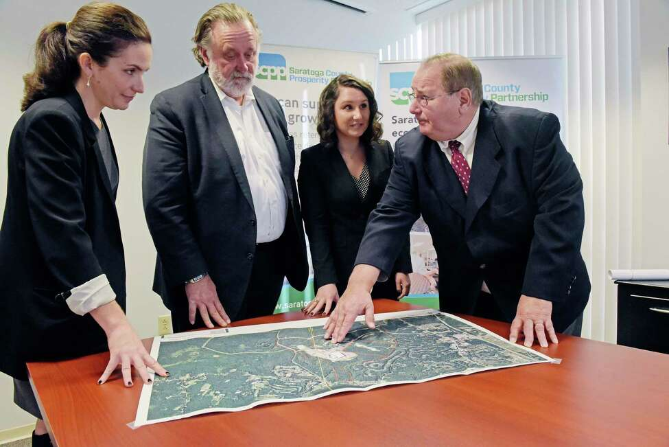 Shelby Schneider, left, VP of Saratoga County Prosperity Partnership, Marty Vanags, second from left, president of Prosperity Partnership and Jenney Kelley, third from left, an economic development assistant with Prosperity Partnership, look over a map of Luther Forest with Kelley's father, Jack Kelley, director of economic development at Prime Companies, on Wednesday, Dec. 19, 2018, in Malta, N.Y. (Paul Buckowski/Times Union)