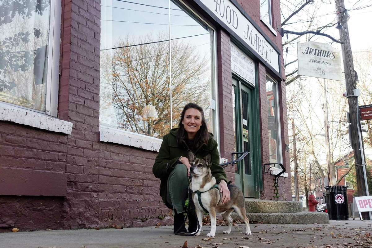 Haley Priebe and her dog Zucca pose for a photo outside of Arthur's Market in the Stockade neighborhood on Wednesday, Dec. 19, 2018, in Schenectady, N.Y. Priebe just recently purchased the building. (Paul Buckowski/Times Union)