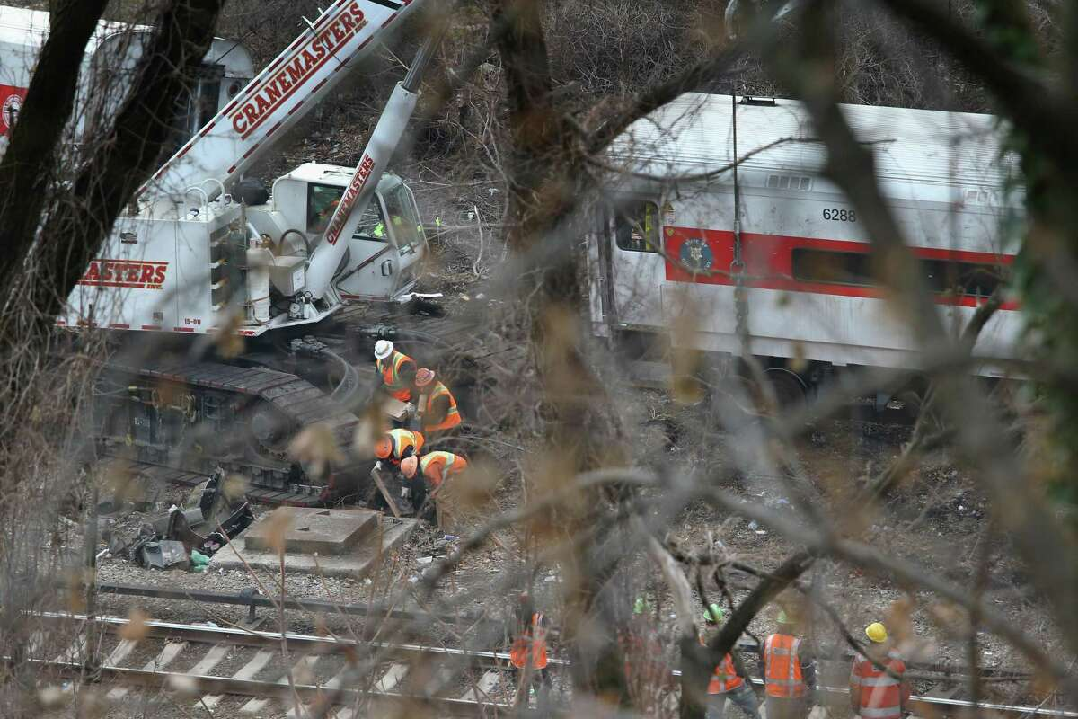 In a 2013 file photo, a rail crew worked at the scene of the fatal Metro-North train derailment in the Bronx borough of New York City. Gov. Dannel P. Malloy on Wednesday announced that all Connecticut rail lines have been equipped with a safety system called Positive Train Control.