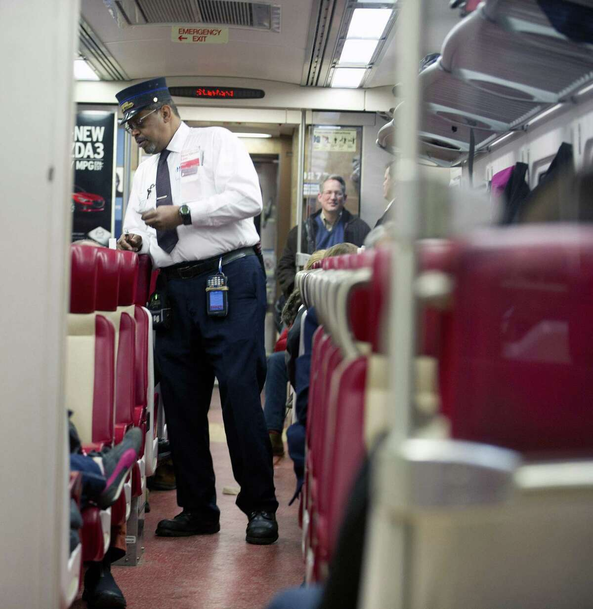 In a file photo, a conductor takes tickets on a Metro-North train. Gov. Dannerl P. Malloy announced Wednesday that all Connecticut train lines now have an added safety system called Positive Train Control. However, the automatic-stop function is not finalized for the possible case of two trains headed toward each other on the same track.