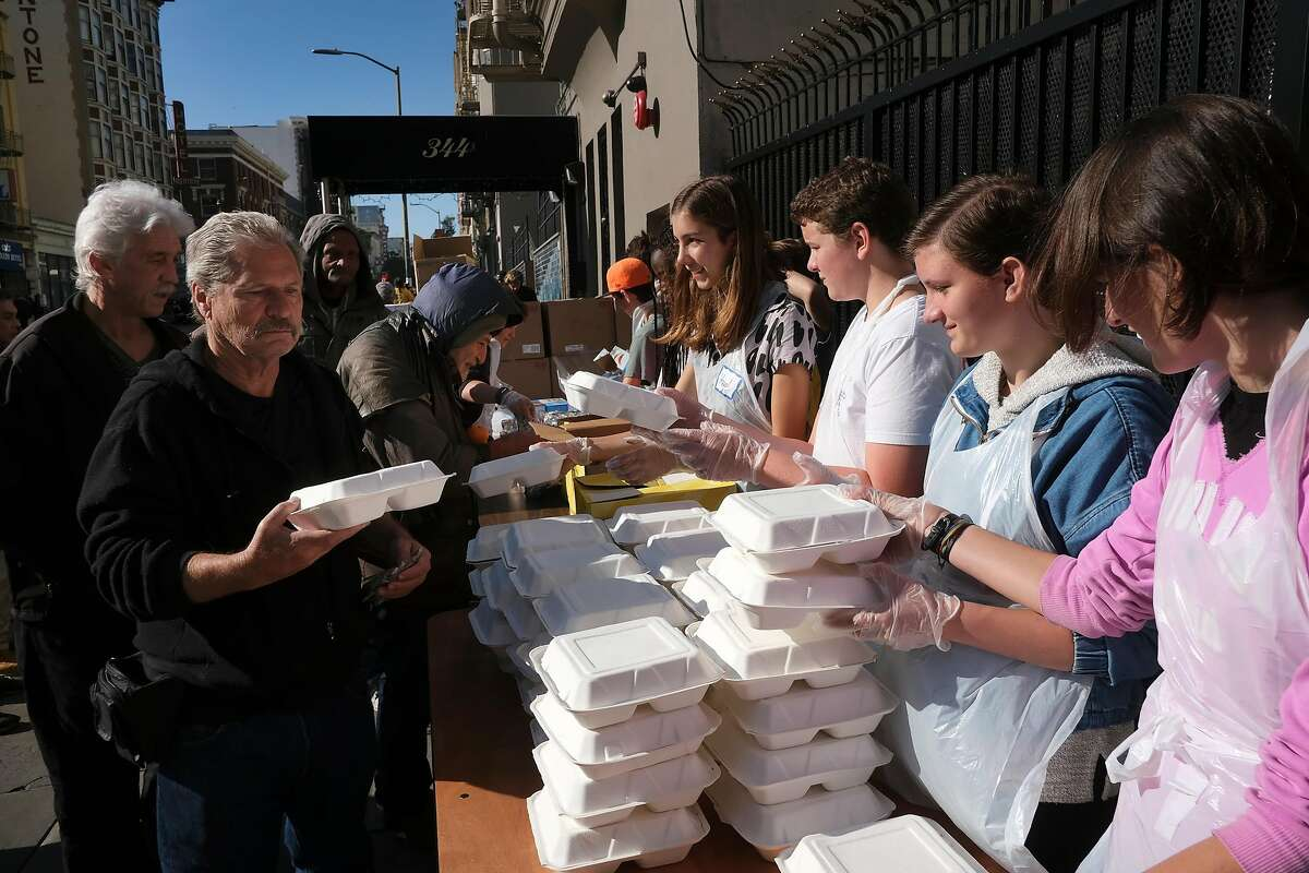 Students from New Village School in Sausalito volunteer handing out free meals outside Glide Memorial Church in San Francisco, California, on Wednesday, December 12, 2018. The United Methodist Church is suing Glide Memorial Church seeking a court order �preserving the UMC�s control over trust property in accordance with the original intent of Lizzie Glide, a devout Methodist who established a trust in 1929 for the express purpose of building a Methodist church for Christian witness and service in San Francisco in honor of her late husband.�