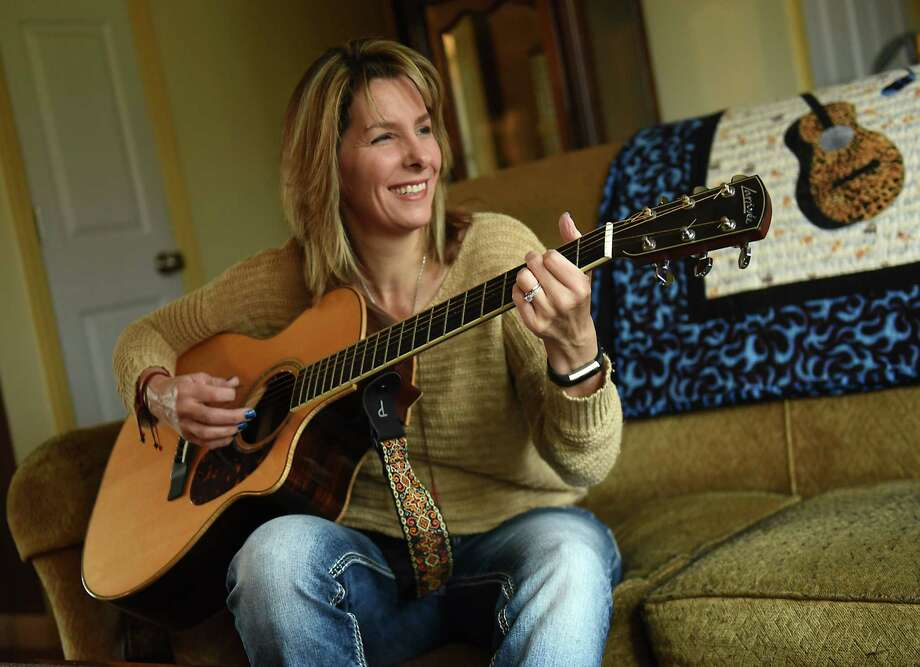Kim Wickham plays her guitar at her home on Friday, Dec. 14, 2018 in Glenmont, N.Y. Wickham was a Syracuse University student studying in London in fall 1988 and had a flight home on Pan Am flight 103 on Dec. 21 but decided to stay abroad for the holidays. Many of her friends died when the flight was destroyed by a bomb over Lockerbie, Scotland. (Lori Van Buren/Times Union) Photo: Lori Van Buren, Albany Times Union / 20045682A
