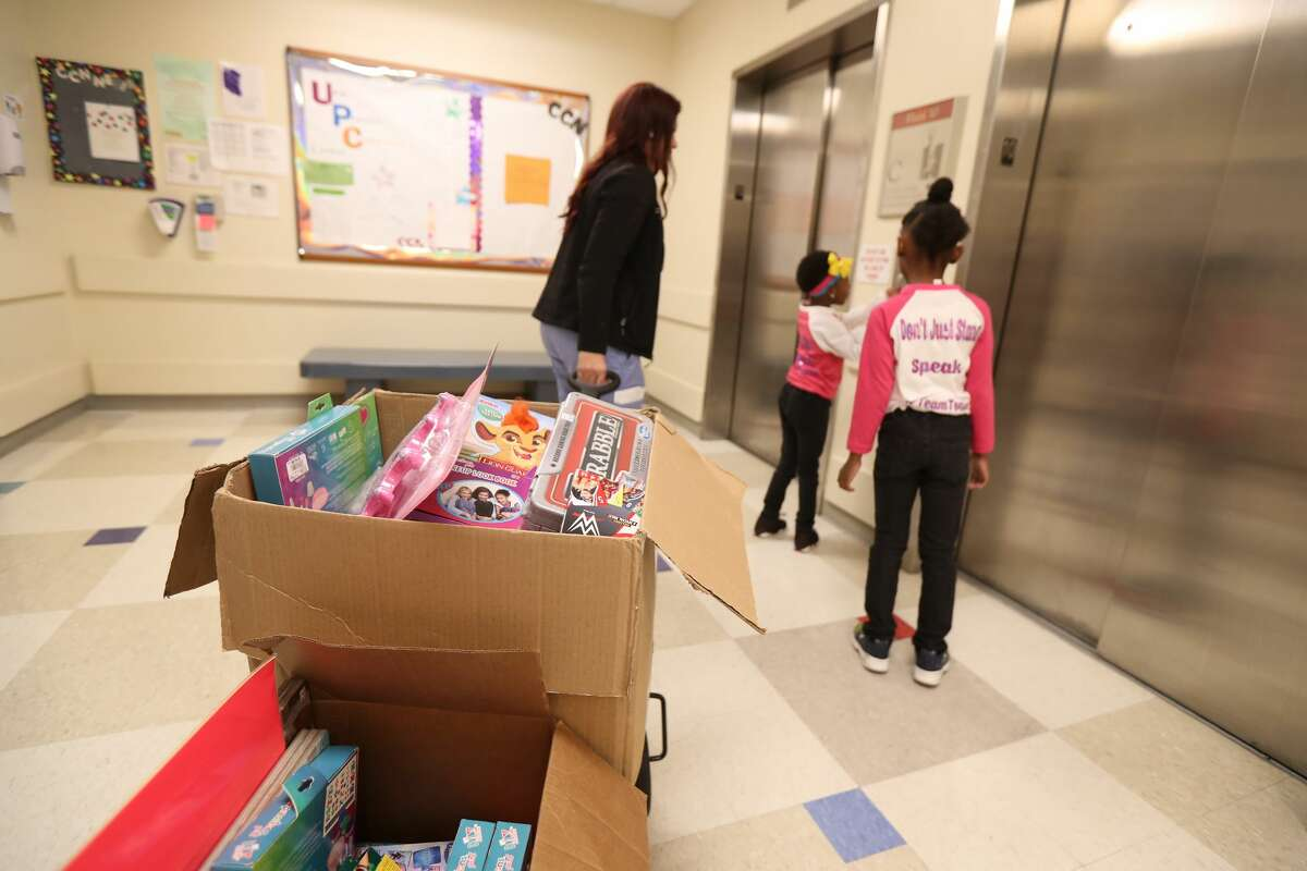 Giovaona Trainor pulls a wagon full of gifts that Tonia Martinez, 5, Kaelah Howard, 7, collected for hospitalized children at Children?'s Memorial Hermann Hospital.