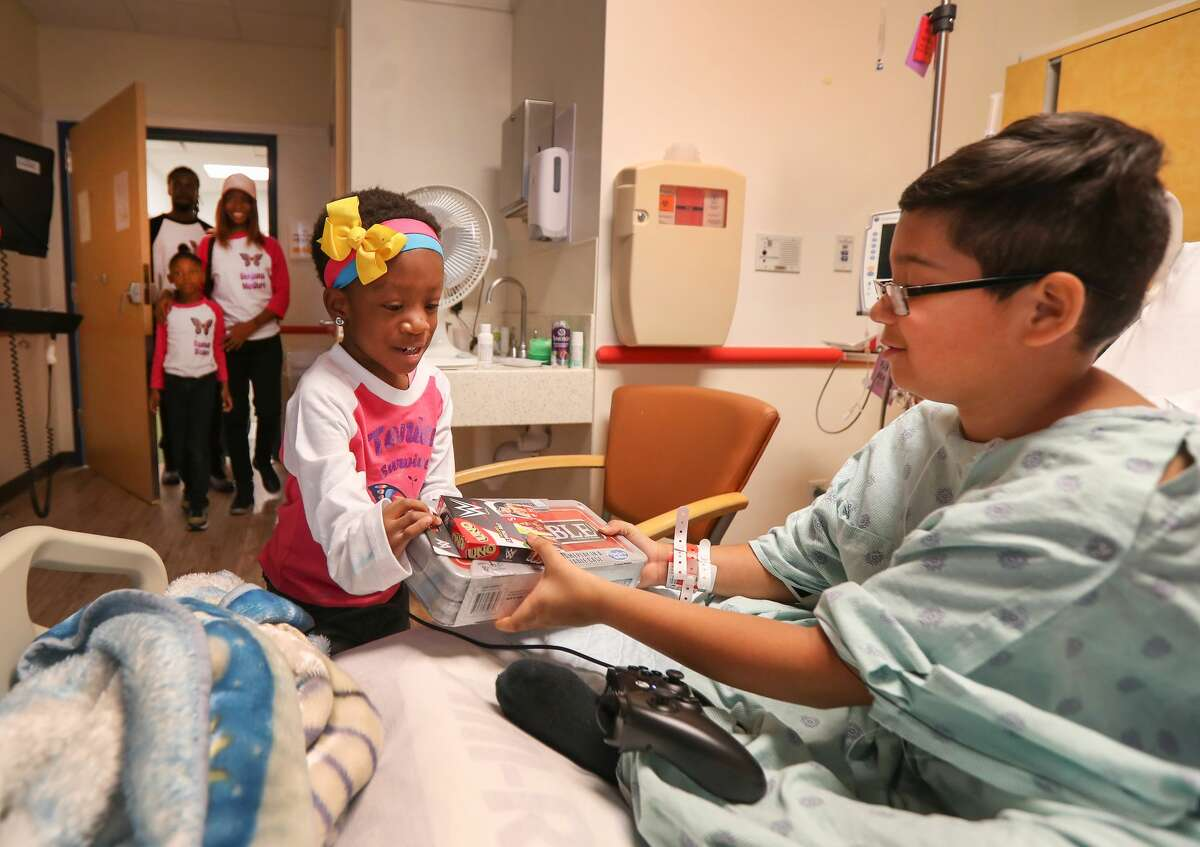 Tonia Martinez, 5, hands out toys to Gustavo Vasquez, 10, as she delivered toys she collected for children at Children?'s Memorial Hermann Hospital Friday, Dec. 14, 2018, in Houston.