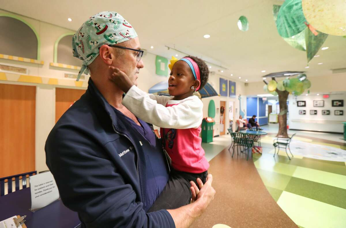 Tonia Martinez, 5, rubs the face of Dr. Matthew Greives, pediatric plastic and craniofacial surgeon at Children?'s Memorial Hermann Hospital Friday, Dec. 14, 2018, in Houston.