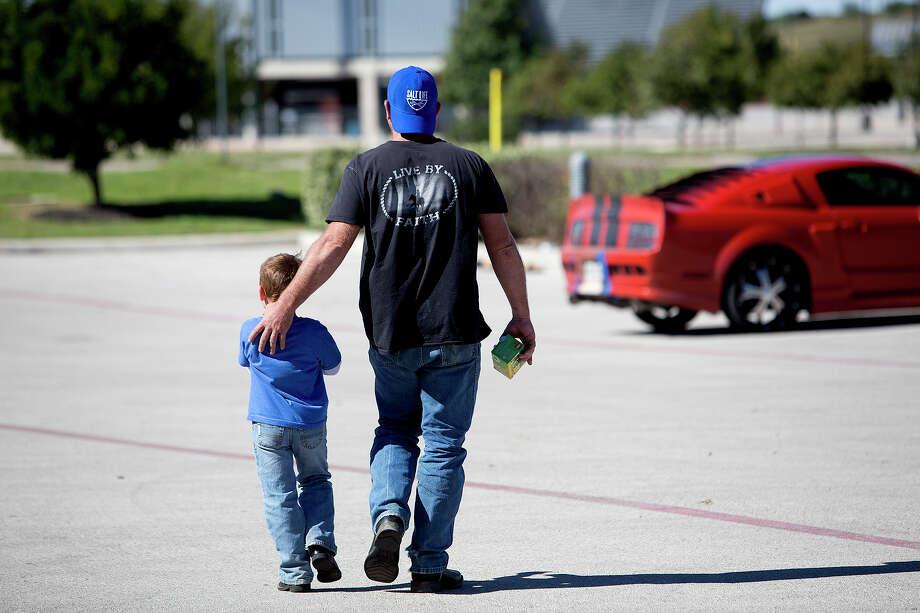 Ryland Ward and his father Chris return to their car after occupational therapy at Children's Rehabilitation Institute TeletonUSA. Photo: Lisa Krantz, San Antonio Express-News / San Antonio Express-News