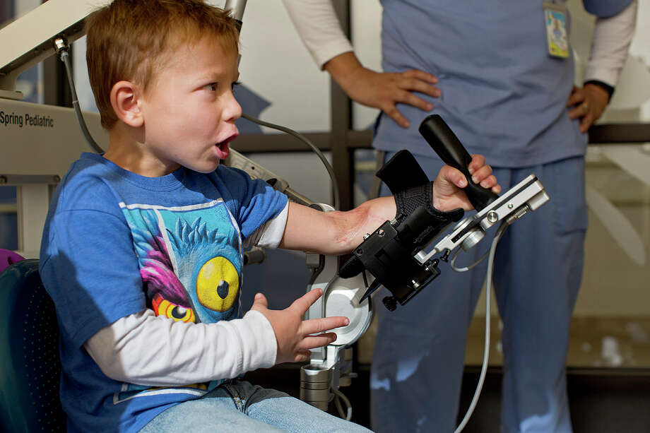 Ryland Ward plays a video game as part of his occupational therapy at Children's Rehabilitation Institute TeletonUSA. Photo: Lisa Krantz, San Antonio Express-News / San Antonio Express-News