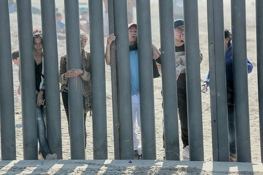 (FILES) In this file photo taken on November 18, 2018, would-be migrants to the United states from Honduras peer through the fence demarcating the US-Mexico border in San Ysidro, California. - The US Senate plans to pass an emergency short-term spending bill as early as Wednesday, December 19, 2018 that averts a looming government shutdown, but excludes the $5 billion that President Donald Trump sought for a US-Mexico border wall. (Photo by Sandy Huffaker / AFP)SANDY HUFFAKER/AFP/Getty Images Photo: SANDY HUFFAKER, Contributor / AFP/Getty Images / AFP or licensors
