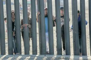 (FILES) In this file photo taken on November 18, 2018, would-be migrants to the United states from Honduras peer through the fence demarcating the US-Mexico border in San Ysidro, California. - The US Senate plans to pass an emergency short-term spending bill as early as Wednesday, December 19, 2018 that averts a looming government shutdown, but excludes the $5 billion that President Donald Trump sought for a US-Mexico border wall. (Photo by Sandy Huffaker / AFP)SANDY HUFFAKER/AFP/Getty Images