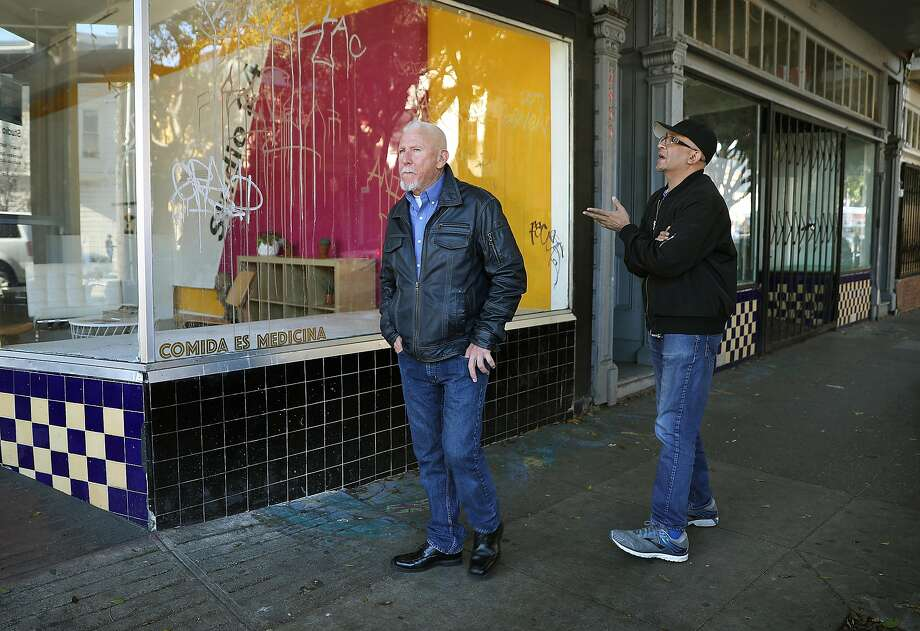 Artist Vikram Lulla (right), upset that the Galería de la Raza is losing its home, brings a friend to visit the space. Photo: Liz Hafalia / The Chronicle