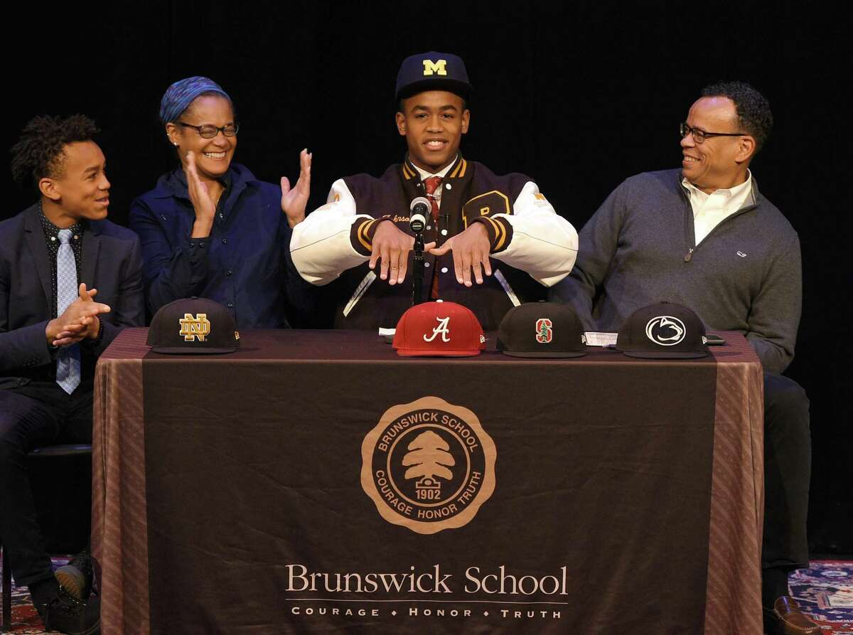 Brunswick senior wide receiver Cornelius Johnson, of Greenwich, formally announces his commitment to play football at the University of Michigan beside his parents Cassandra Tribble, M.D. and Claude Johnson, and brother Carnegie Johnson, 14, at Brunswick School in Greenwich, Conn. Wednesday, Dec. 19, 2018. Johnson is a 6-foot-3, 198-pound 4-star prospect who caught 50 passes for 826 yards and 12 touchdowns in his senior season.