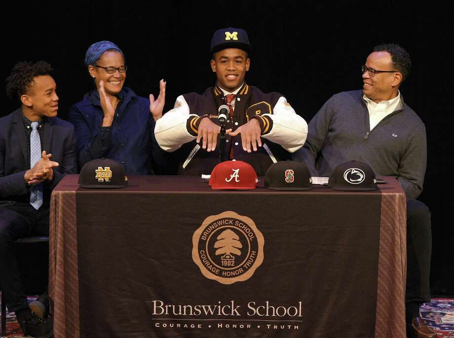 Brunswick senior wide receiver Cornelius Johnson, of Greenwich, formally announces his commitment to play football at the University of Michigan beside his parents Cassandra Tribble, M.D. and Claude Johnson, and brother Carnegie Johnson, 14, at Brunswick School in Greenwich, Conn. Wednesday, Dec. 19, 2018. Johnson is a 6-foot-3, 198-pound 4-star prospect who caught 50 passes for 826 yards and 12 touchdowns in his senior season. Photo: Tyler Sizemore / Hearst Connecticut Media / Greenwich Time