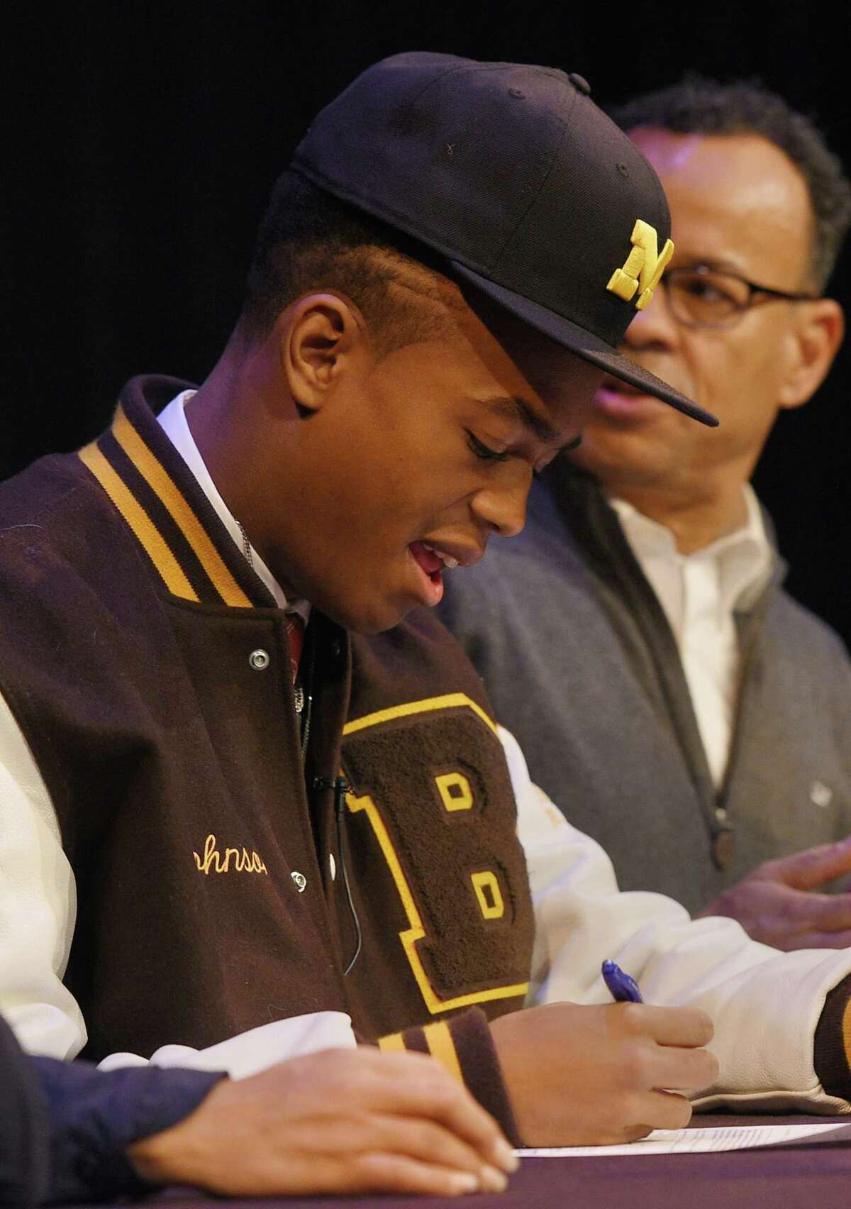 Brunswick senior wide receiver Cornelius Johnson, of Greenwich, signs his letter of intent to play football at the University of Michigan beside his parents Cassandra Tribble, M.D. and Claude Johnson, and brother Carnegie Johnson, 14, at Brunswick School in Greenwich, Conn. Wednesday, Dec. 19, 2018. Johnson is a 6-foot-3, 198-pound 4-star prospect who caught 50 passes for 826 yards and 12 touchdowns in his senior season.