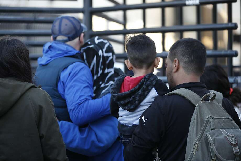 In this Dec. 18, 2018 photo, Honduran asylum seekers enter the U.S. at San Diego's Otay Mesa port of entry, as seen from Tijuana, Mexico.  A federal judge has blocked restrictive Trump administration policies that prevented some immigrants from seeking asylum due to domestic and gang violence in their home countries. (AP Photo/Moises Castillo) Photo: Moises Castillo, Associated Press