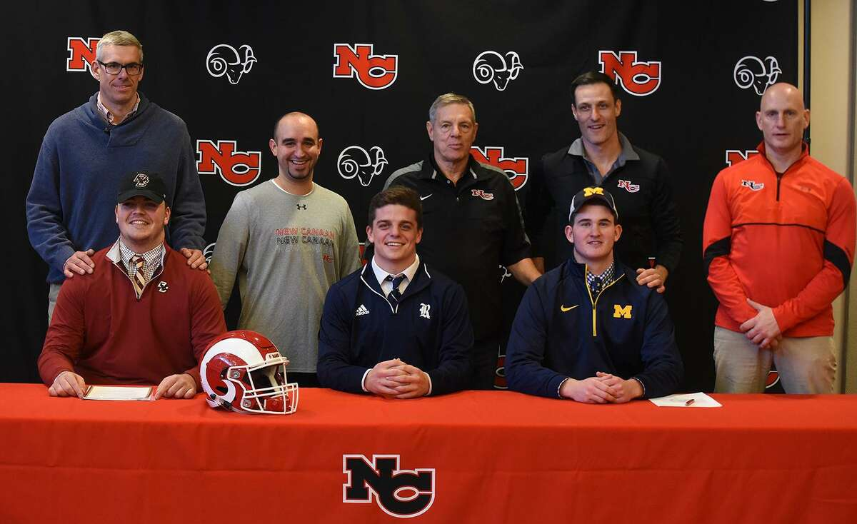 New Canaan football coaches with, from left, front row, Jack Conley, Garrett Braden and Jack Stewart, who signed their National Letters of Intent on Wed., Dec. 19, 2018 at NCHS. Back row, from left, Ben Velishka, AJ Albano, head coach Lou Marinelli, Chris Silvestri, and Jason Miska. ?- Dave Stewart photo
