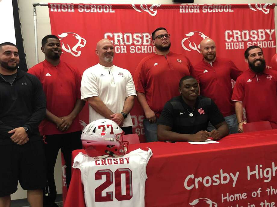 Crosby offensive guard Chayse Todd celebrates with his coaches signing his National Letter of Intent to play football at the University of Houston on Dec.19 Photo: Elliott Lapin / Staff Photo
