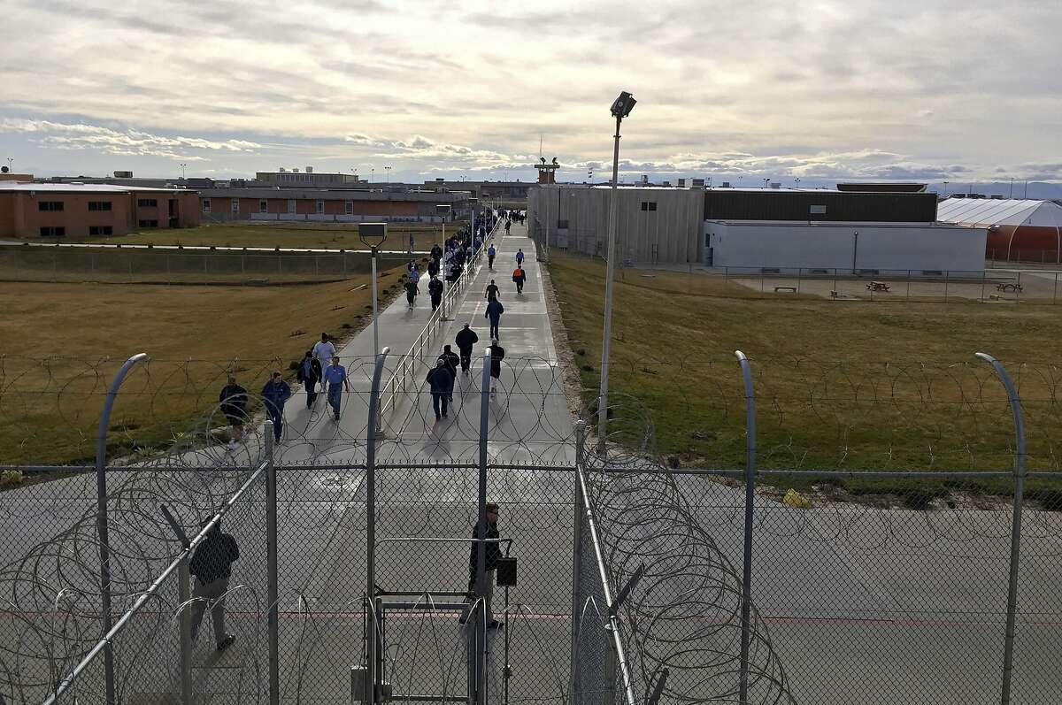 """FILE - In this Jan. 30, 2018 file photo, inmates walk across the grounds of the Idaho State Correctional Institution in Kuna, Idaho. Idaho transgender inmate Adree Edmo has spent most of her prison term at this men's prison facility. A federal judge ruled Thursday, Dec. 13, 2018 that the state must provide Edmo with gender confirmation surgery to make her physical characteristics match her gender identity as a woman."""" (AP Photo/Rebecca Boone, File)"""