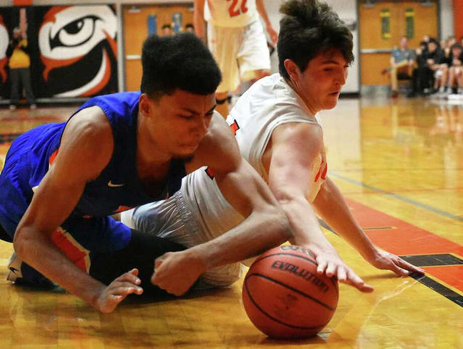 Edwardsville forward Nick Hemken reaches for a loose ball while on the court during the first half against East St. Louis on Wednesday in Edwardsville. Photo: Matt Kamp/Intelligencer