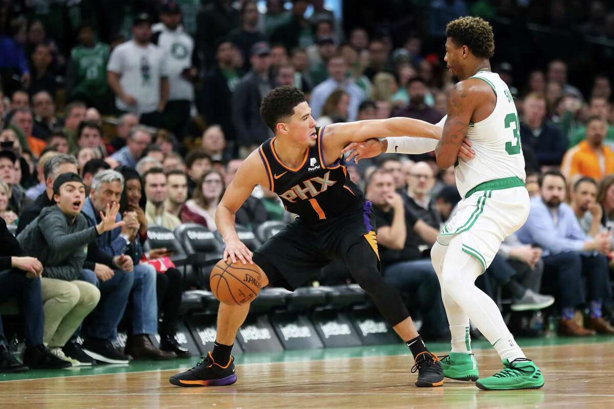 BOSTON, MASSACHUSETTS - DECEMBER 19: Marcus Smart #36 of the Boston Celtics defends Devin Booker #1 of the Phoenix Suns at TD Garden on December 19, 2018 in Boston, Massachusetts. The Suns defeat the Celtics 111-103. NOTE TO USER: User expressly acknowledges and agrees that, by downloading and or using this photograph, User is consenting to the terms and conditions of the Getty Images License Agreement. (Photo by Maddie Meyer/Getty Images)