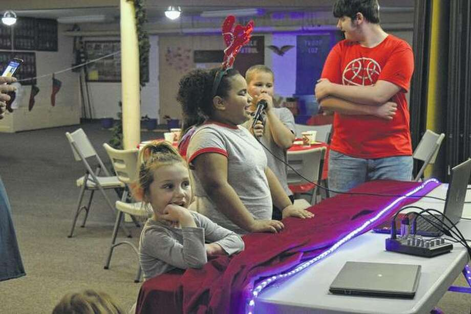 Cora Keefe, 5, along with Jazlynn Haynes, 9, and Lionel Haynes, 9, sing along Tuesday to Christmas songs at Grace United Methodist Church's Christmas Celebration. Photo: Audrey Clayton | Journal-Courier