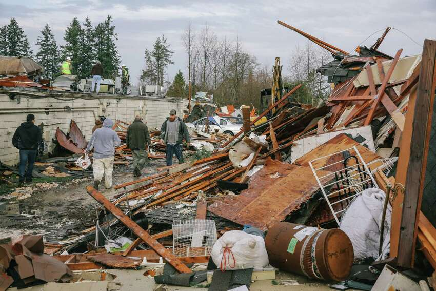 People help to clean up debris from the destruction of Salmon Berry Dry Storage after Tuesday's tornado in Port Orchard, Wednesday, Dec. 19, 2018.