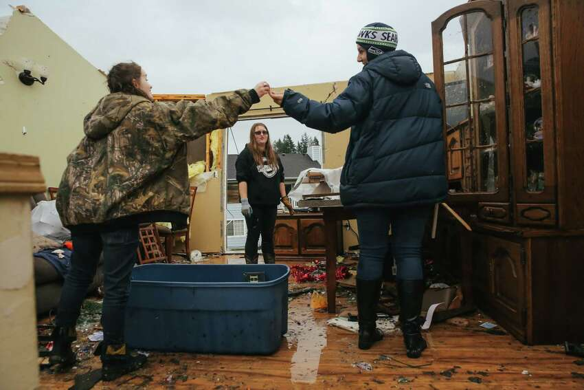 Jasmin Mueller, 16, left, is handed a key by her aunt Melinda St. John, right, as Mueller's sister Hannah, 20, helps to clean up after a tornado tore the roof off of their house Tuesday in Port Orchard, Wednesday, Dec. 19, 2018.