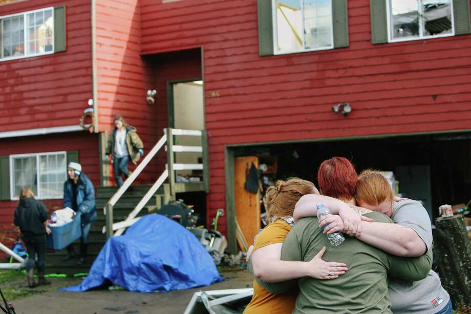 Tawnia Cope-Crain holds her daughters Morgan and Tamlyn Crain outside their house, which sustained significant damage in Tuesday's tornado in Port Orchard as neighbors move their belongings out of the house next door, Wednesday, Dec. 19, 2018. Cope-Crain was home with her husband and older daughter at the time of the tornado. Photo: GENNA MARTIN, GENNA MARTIN, SEATTLEPI.COM / SEATTLEPI.COM