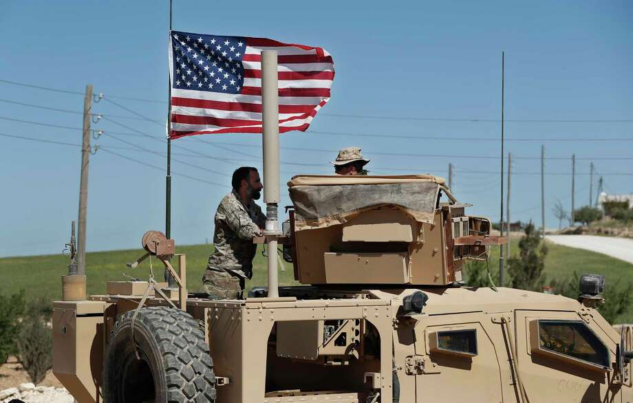In this April 4, 2018 photo, a U.S-backed Syrian Manbij Military Council soldier, left, speaks with a U.S. soldier, at a U.S. position near the tense front line with Turkish-backed fighters, in Manbij town, north Syria. Photo: Hussein Malla, AP / Copyright 2018 The Associated Press. All rights reserved.