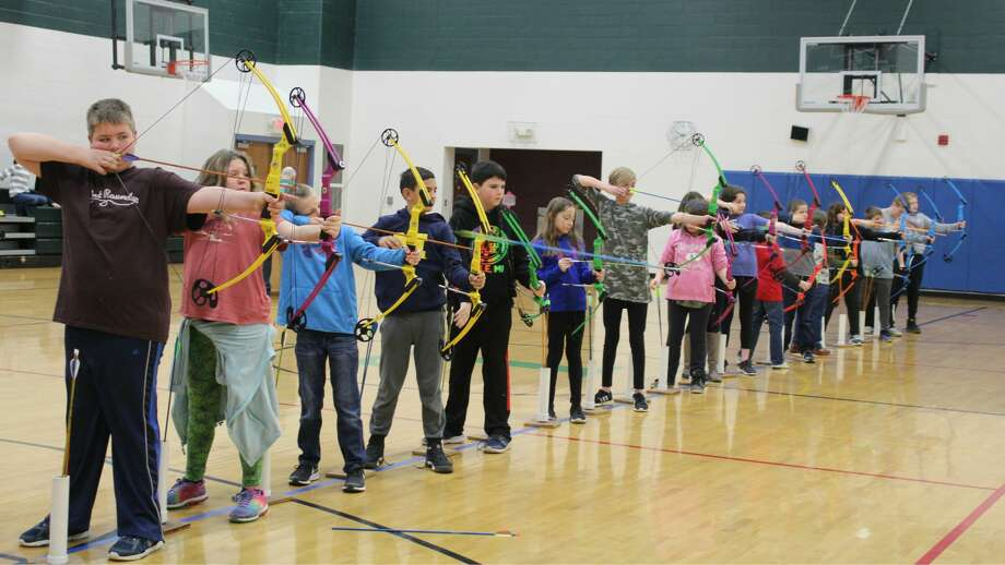 Laker fifth graders learn archery skills in gym class, with the assistance of Laker Archery Coach Lyle Gascho and Laker Elementary gym teacher Josh Fuller. For Laker fourth and fifth graders interested in archery, team practice will begin after the holiday break. The archery team did very well last year, making it all the way to the NASP World Tournament. Photo: Submitted Photo