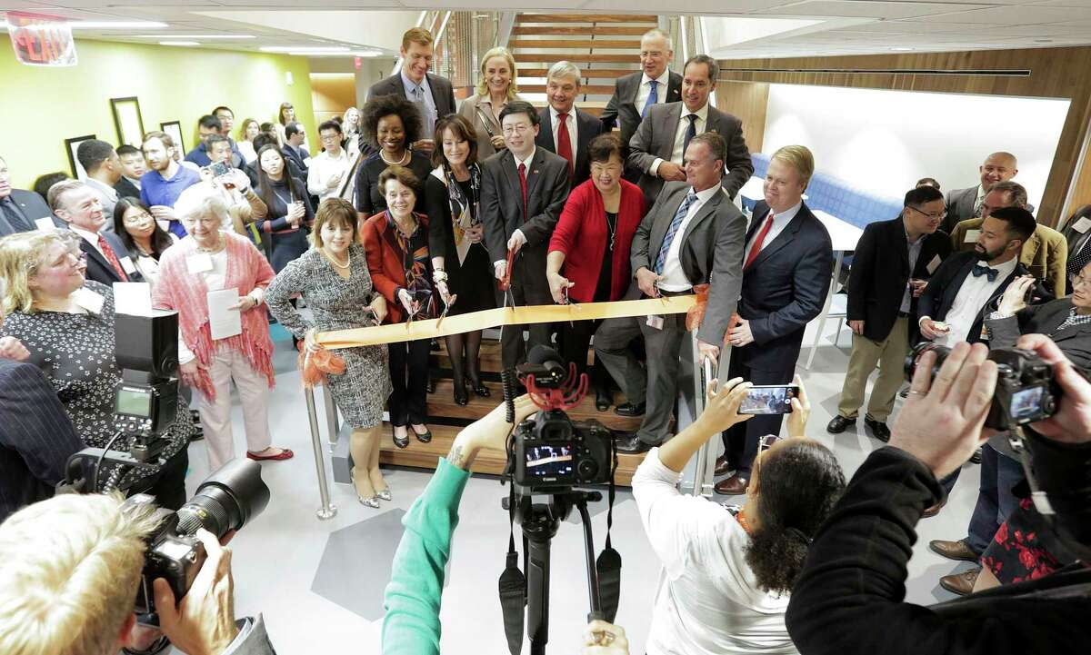 Dignitaries fill in around UTHealth School of Biomedical Informatics Dean JiaJie Zhang as he cuts the ribbon during a ribbon-cutting ceremony for the new $15 million UTHealth School of Biomedical Informatics building in Houston on Wednesday, Dec. 19, 2018.
