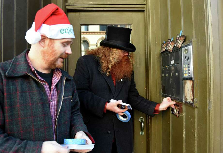 "Troy Councilman Anasha Cummings, right, and Duncan Crary, his communications manager, left, deliver Christmas cards to Second Street constituents on Thursday, Dec. 20, 2018, in Troy, N.Y. The cards feature a photograph of Cummings dressed as the Ghost of Christmas Present in a depiction of Charles Dickens' ""A Christmas Carol,"" where he appears with other characters from the story. (Will Waldron/Times Union) Photo: Will Waldron, Albany Times Union / 20045779A"