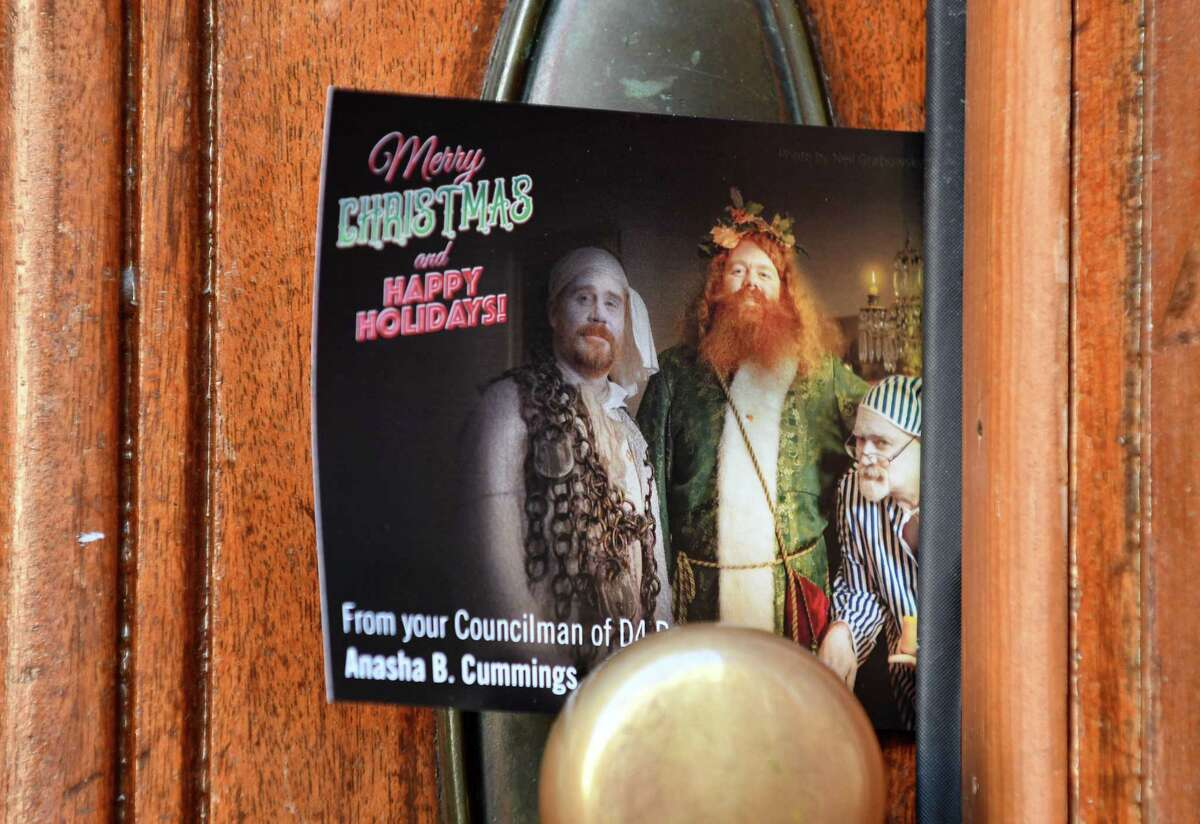 A Christmas card from, and featuring, Troy Councilman Anasha Cummings is left at a Second Street home on Thursday, Dec. 20, 2018, in Troy, N.Y. The cards feature a photograph of Cummings dressed as the Ghost of Christmas Present in a depiction of Charles Dickens'