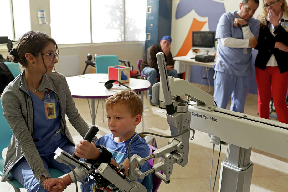 UT Health San Antonio student Katherine Garcia works with Ryland Ward while his occupational therapist, Rudy Cardenas, talks with Dr. Cynthia Riley. Ryland's father, Chris Ward, watches during occupational therapy at Children's Rehabilitation Institute TeletonUSA. Photo: Lisa Krantz / San Antonio Express-News