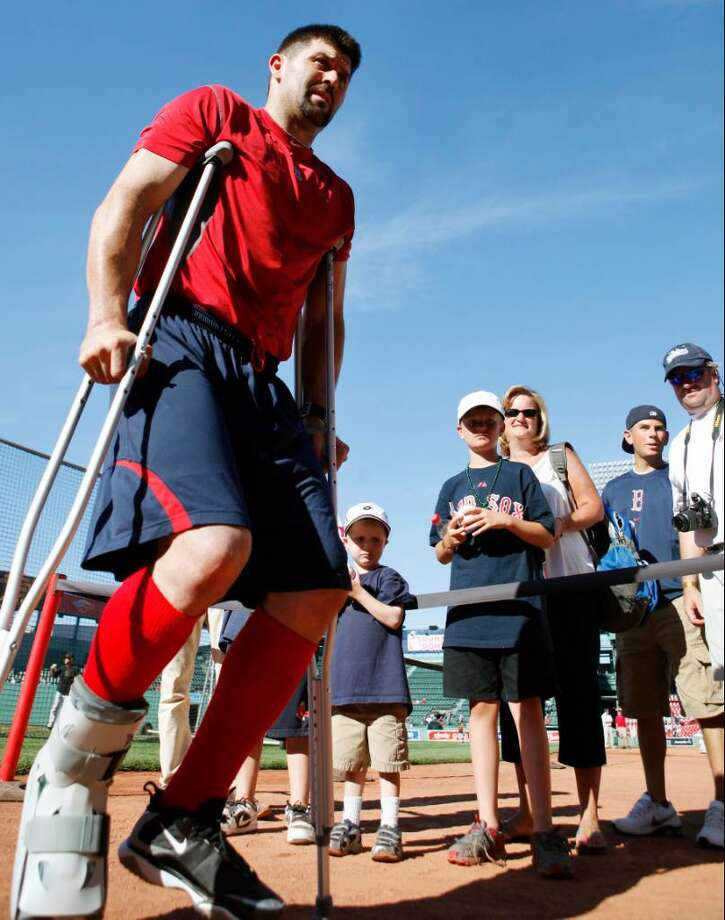 FILE-This July 3, 2010 file photo shows Boston Red Sox's Jason Varitek leaving  the field on crutches after batting practice before a baseball game between the Red Sox and the Baltimore Orioles in Boston. The floor of the Red Sox clubhouse was filled with black equipment bags as players packed for their 10-day West Coast trip. Amid the clutter, the stuff that revealed the team's current condition was still hard to miss. The protective boot on Dustin Pedroia's broken left foot. The splint on Victor Martinez's fractured left thumb. The crutches leaning against Varitek's locker, and the boot on his broken right foot. (AP Photo/Michael Dwyer,File) Photo: AP