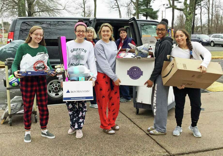 Mercy High School students take in donations and sort items for the Albert Solnit Children's Center in Middletown. From left are Mercy National Honor Society officers and Solnit staff: Abby Smith, treasurer; Annmarie Rotatori, vice president of committees; Elaine Jackson, Solnit; Kaitlin Leahy, president; Melanie Clark, Solnit; Catryn Rhoden, vice president of tutoring; and Bianca LaBella, secretary. Photo: Contributed Photo
