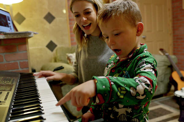 Ryland Ward plays piano with music therapist Elisabeth Hand at The Ecumenical Center's Center for Healing & Hope of South Texas in La Vernia.