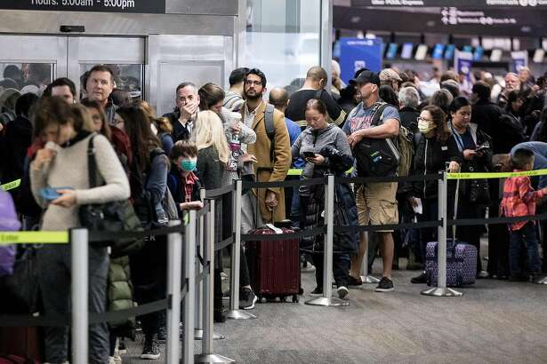 Hundreds of passengers wait to go through a TSA security checkpoint before catching their flights at San Francisco International Airport in San Francisco, Calif. Wednesday, Dec. 19, 2018.