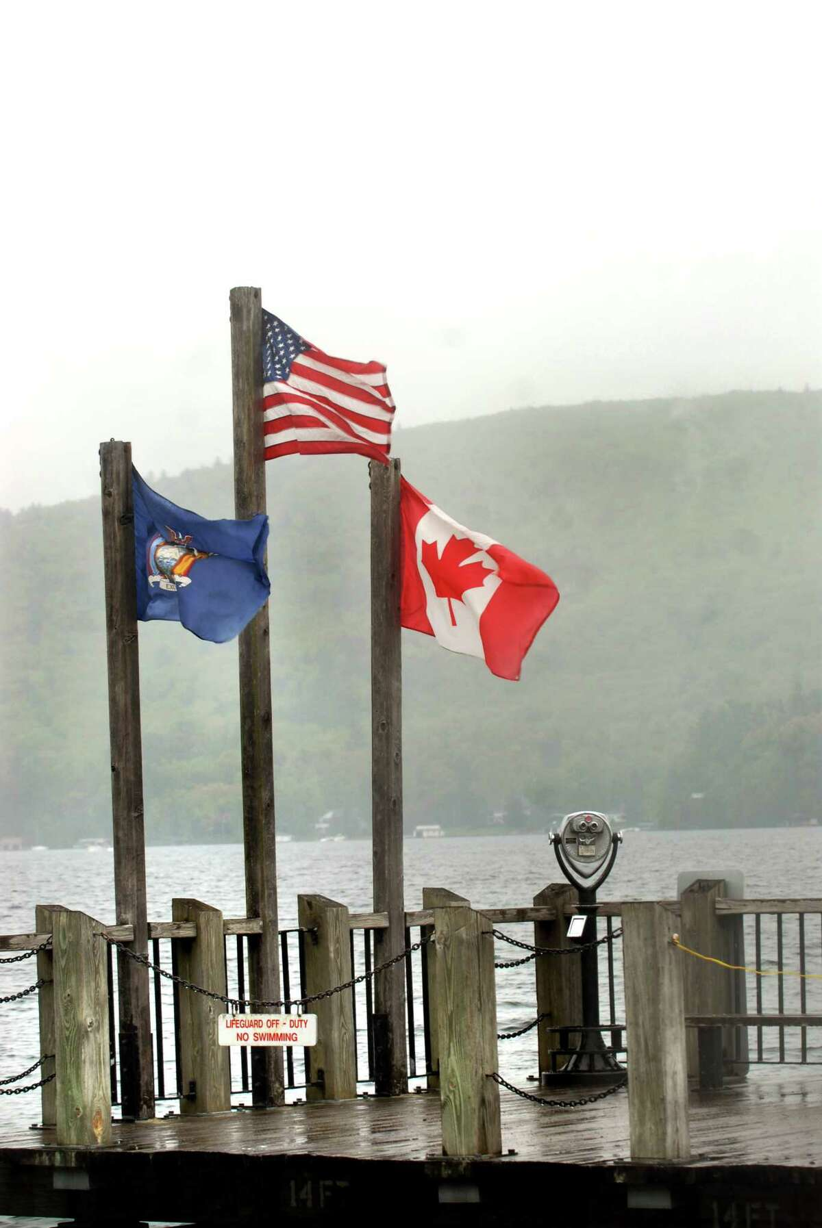 Despite sagging Canadian opinions about the United States and President Donald Trump, business and tourism ties between New York and Canada appeared not to have suffered this summer, according to officials. Here, the Canadian flag flies with the U.S. flag and the New York State flag on the public dock at the tourist destination of Lake George. (Times Union archive)