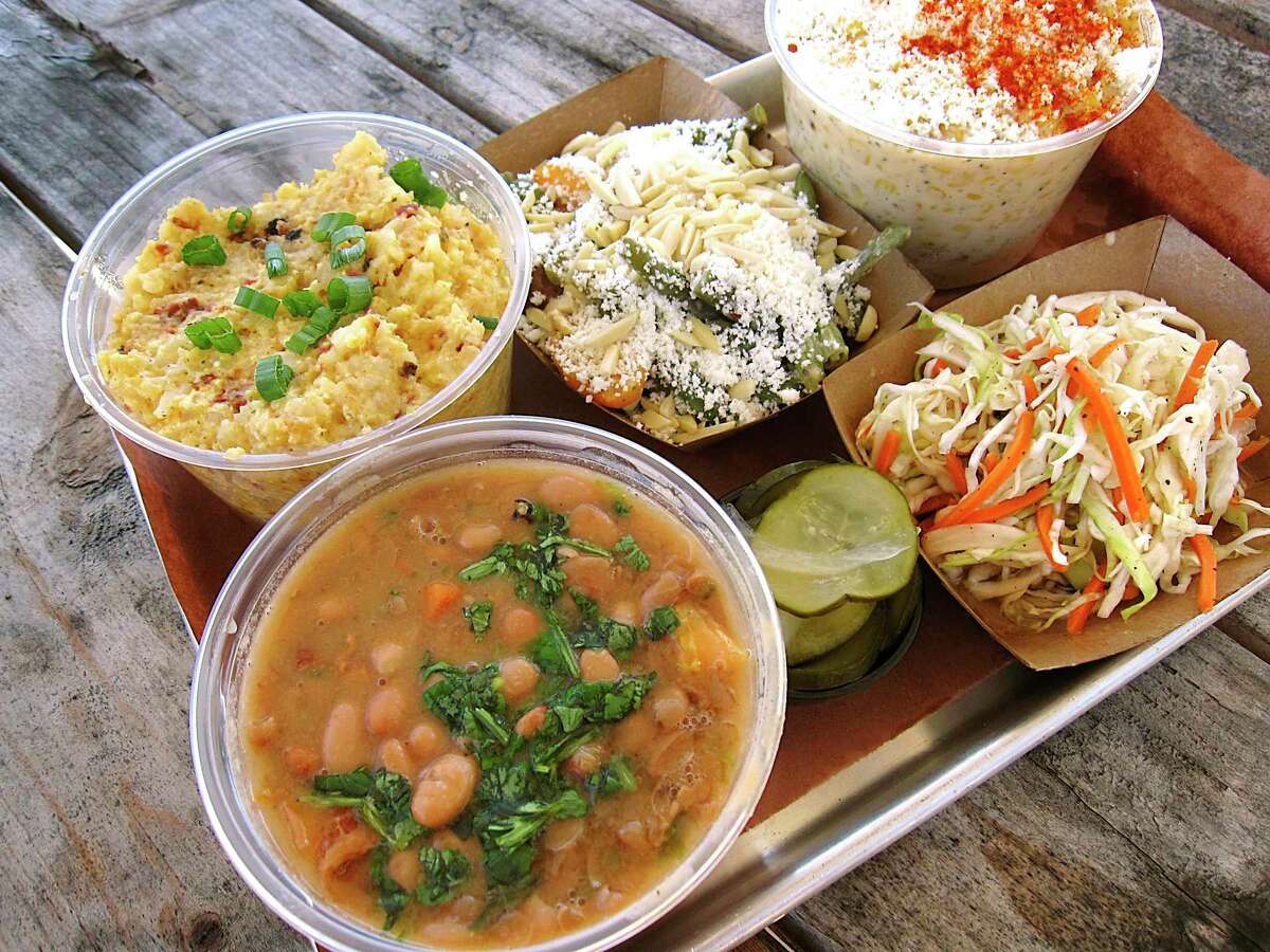 Side dishes of borracho beans, loaded tater tor casserole, green bean salad, creamed corn, slaw and pickles from South BBQ & Kitchen.