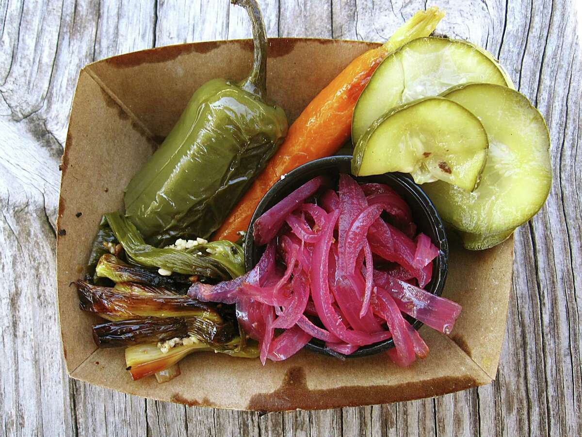 Pickled jalapeño, carrot, cucumbers and onions with roasted green onions from South BBQ & Kitchen.