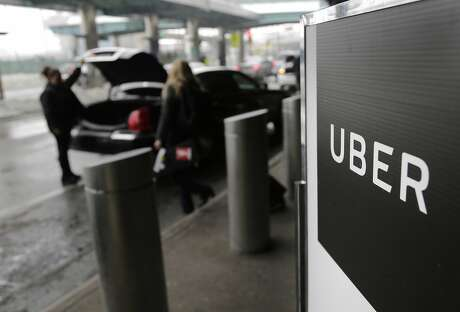 FILE - In this March 15, 2017, file photo, a sign marks a pick up point for the Uber car service at LaGuardia Airport in New York. Uber will resume testing autonomous vehicles in an area near Downtown Pittsburgh starting Thursday, Dec. 20, 2018. (AP Photo/Seth Wenig, File)