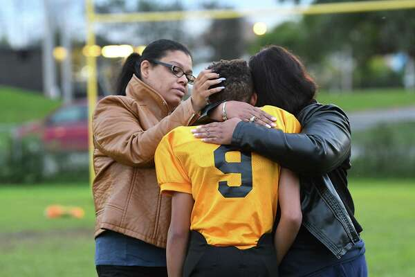 Jalen McLean, 12, is comforted by his mother Jamie Hawley, right, and another mother of a teammate Marurisa Hyler, left. (Lori Van Buren/Times Union)