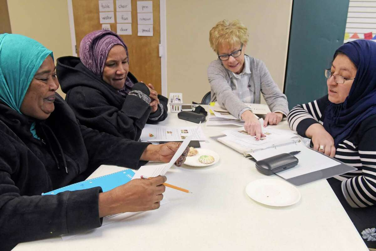 Ibtesam Mahed, left, from Sudan, Mawa Toum, second from left, also from Sudan and Naseema Qayumi, right, from Afghanistan, work with volunteer, Paula Johannessen as they learn English at the Refugee Welcome Center on Tuesday, Dec. 18, 2018, in Albany, N.Y. (Paul Buckowski/Times Union)